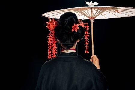 Foto de Vista trasera de hermosa geisha en kimono negro con flores rojas en el pelo sosteniendo paraguas asiático tradicional aislado en negro - Imagen libre de derechos
