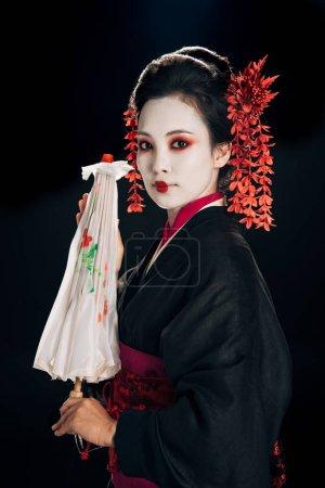 Photo pour Belle geisha dans le kimono noir avec des fleurs rouges dans le cheveu retenant le parapluie asiatique traditionnel d'isolement sur le noir - image libre de droit