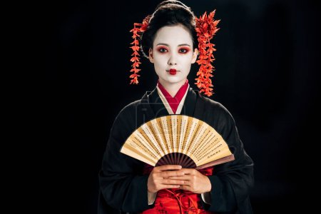 Photo pour Geisha en kimono noir avec des fleurs rouges dans les cheveux tenant traditionnel asiatique main ventilateur isolé sur noir - image libre de droit