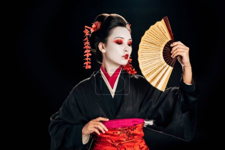 Photo for Geisha in kimono with red flowers in hair holding traditional asian hand fan isolated on black - Royalty Free Image