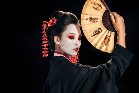 Photo for Side view of geisha in black kimono with red flowers in hair holding traditional asian hand fan isolated on black - Royalty Free Image