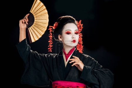 geisha in black kimono with red flowers in hair dancing with traditional asian hand fan isolated on black