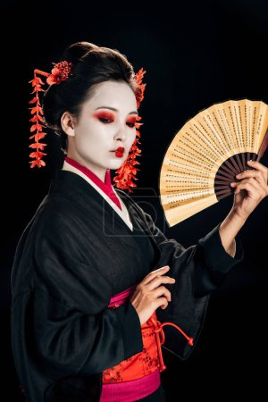 Photo for Geisha in black kimono with red flowers in hair holding traditional asina hand fan isolated on black - Royalty Free Image
