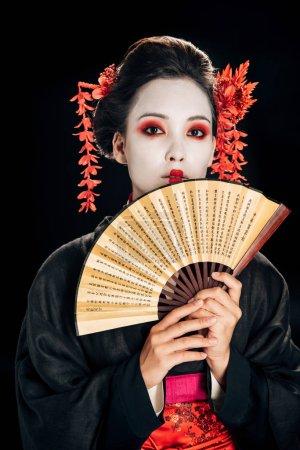 Photo pour Jeune geisha en kimono noir avec des fleurs rouges dans les cheveux tenant traditionnel asiatique main ventilateur isolé sur noir - image libre de droit