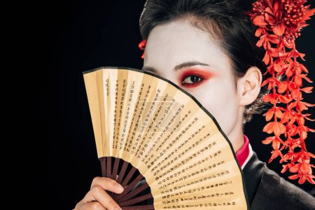 Photo for Young geisha in black kimono with red flowers in hair holding traditional hand fan in front of face isolated on black - Royalty Free Image
