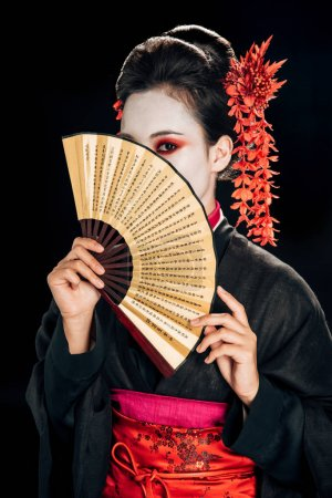 Photo for Geisha in black kimono with red flowers in hair and obscure face holding traditional asian hand fan isolated on black - Royalty Free Image