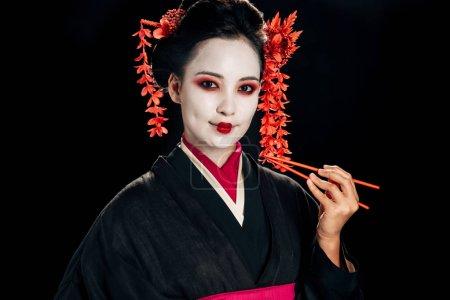 Foto de Sonriendo hermosa geisha en kimono negro con flores rojas en el pelo sosteniendo palillos aislados en negro - Imagen libre de derechos