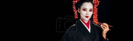 Photo pour Belle geisha de sourire dans le kimono noir avec les fleurs rouges dans les baguettes de fixation de cheveux d'isolement sur le noir, projectile panoramique - image libre de droit