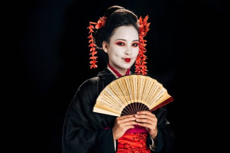 Photo for Cheerful geisha in black kimono with red flowers in hair holding traditional asian hand fan isolated on black - Royalty Free Image