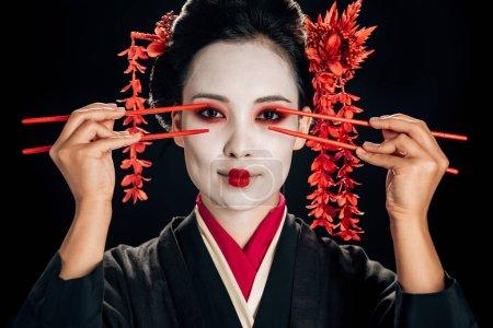 Photo pour Belle geisha en kimono noir avec des fleurs rouges dans les cheveux tenant des baguettes près des yeux isolés sur le noir - image libre de droit