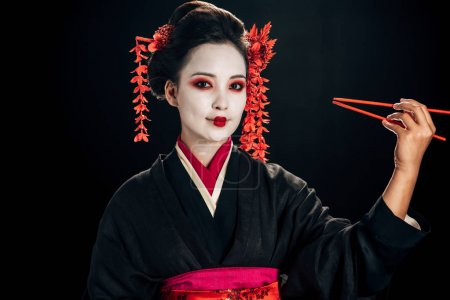 Photo for Cheerful beautiful geisha in black kimono with red flowers in hair holding chopsticks isolated on black - Royalty Free Image