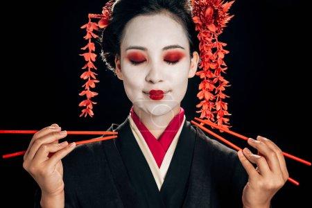 Photo pour Belle geisha de sourire dans le kimono noir avec les fleurs rouges dans les cheveux et les yeux fermés retenant des baguettes d'isolement sur le noir - image libre de droit