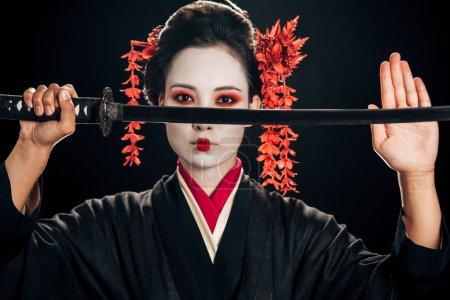 Photo pour Geisha confiant dans le kimono noir avec les fleurs rouges dans le katana de fixation de cheveux d'isolement sur le noir - image libre de droit