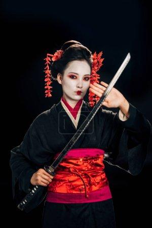 Photo pour Belle geisha en kimono noir avec des fleurs dans les cheveux tenant katana isolé sur le noir - image libre de droit
