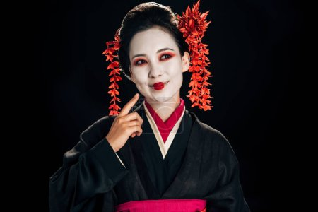 Photo pour Vue de côté de la belle geisha heureuse dans le kimono noir et rouge et les fleurs dans le cheveu pointant avec le doigt au visage d'isolement sur le noir - image libre de droit