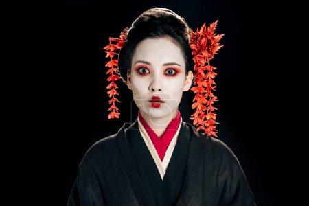 Photo pour Choqué belle geisha en kimono noir et rouge et des fleurs dans les cheveux isolés sur le noir - image libre de droit