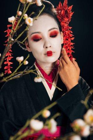 Photo pour Foyer sélectif de belle geisha dans le kimono noir avec les fleurs rouges dans le visage touchant de cheveux et les branches de sakura d'isolement sur le noir - image libre de droit