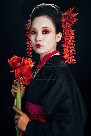 Photo for Beautiful geisha in black kimono with red flowers isolated on black - Royalty Free Image