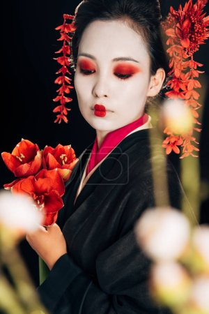 Photo for Selective focus of beautiful geisha in black kimono with red flowers and sakura branches isolated on black - Royalty Free Image