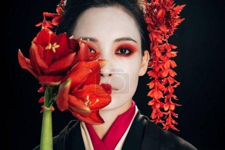 Photo pour Verticale de belle geisha dans le kimono noir avec les fleurs rouges d'isolement sur le noir - image libre de droit