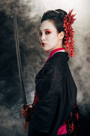 Photo pour Vue latérale de belle geisha dans le katana noir de fixation de kimono dans la fumée sur le fond noir - image libre de droit