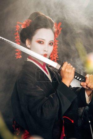Photo pour Mise au point sélective de geisha en kimono noir tenant le katana dans la fumée et les branches de sakura - image libre de droit