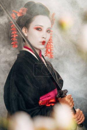 Photo pour Mise au point sélective de geisha grave en kimono noir tenant le katana dans la fumée et les branches de sakura - image libre de droit
