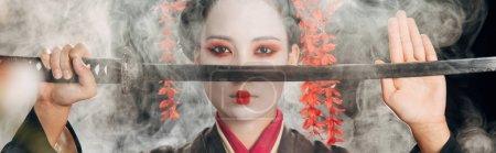 Photo pour Foyer sélectif de belle geisha en kimono noir tenant le katana dans la fumée, projectile panoramique - image libre de droit