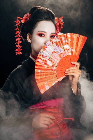 beautiful geisha in black kimono with flowers in hair holding hand fan in smoke