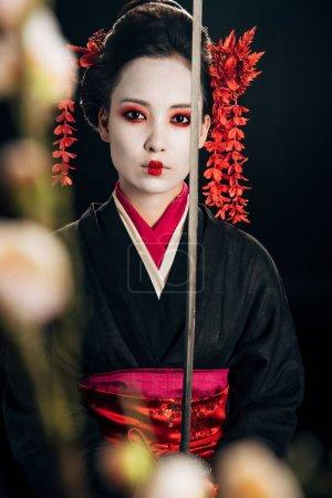 Photo pour Foyer sélectif de geisha confiante dans le kimono noir tenant des branches de katana et de sakura isolées sur du noir - image libre de droit