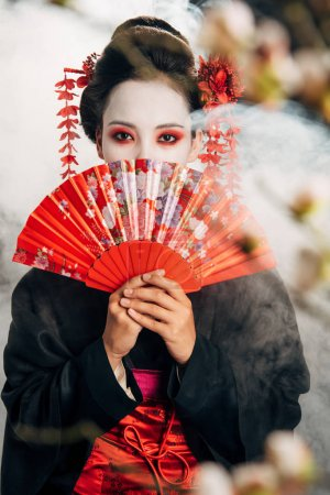 selective focus of beautiful geisha in black kimono with flowers in hair holding hand fan in front of face and sakura branches in smoke