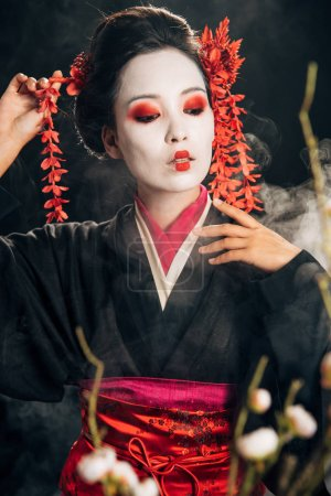 Photo pour Foyer sélectif de belle geisha en kimono noir avec des fleurs rouges dans les cheveux et les branches de sakura sur fond noir avec de la fumée - image libre de droit