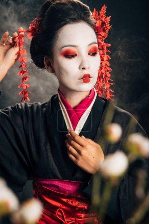 Photo pour Foyer sélectif de geisha dans le kimono noir avec les fleurs rouges dans les cheveux et les branches de sakura sur le fond noir avec la fumée - image libre de droit