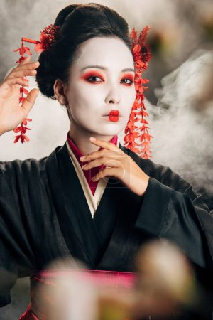 selective focus of geisha in black kimono with red flowers in hair touching face near sakura branches on black background with smoke