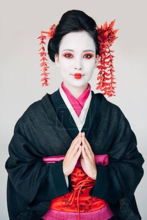 Photo pour Belle geisha de sourire dans le kimono noir avec des mains de salutation d'isolement sur le blanc - image libre de droit