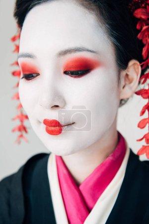 Photo pour Fermer vers le haut la vue de belle geisha de sourire dans le kimono noir avec des fleurs rouges dans le cheveu d'isolement sur le blanc - image libre de droit