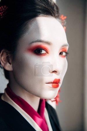 Foto de Retrato de hermosa geisha con maquillaje rojo y blanco mirando a la cámara en la luz del sol - Imagen libre de derechos