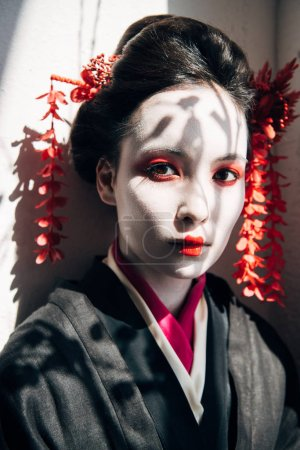 Photo pour Portrait de belle geisha avec maquillage rouge et blanc regardant la caméra au soleil avec des ombres - image libre de droit