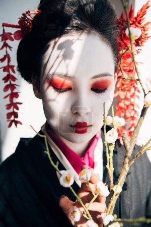 Photo pour Branches de sakura et belle geisha avec le maquillage rouge et blanc dans la lumière du soleil - image libre de droit