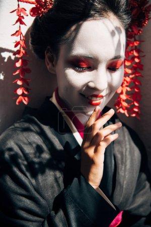 Photo pour Verticale de belle geisha de sourire avec le maquillage rouge et blanc dans la lumière du soleil avec des ombres - image libre de droit