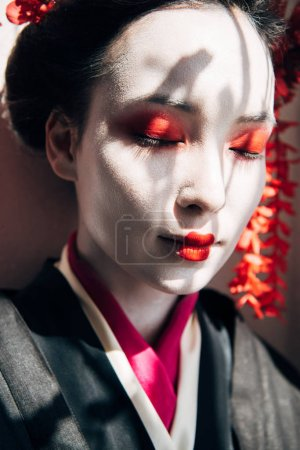 Photo for Portrait of beautiful geisha with red and white makeup and closed eyes in sunlight with shadows - Royalty Free Image