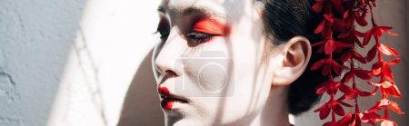 Foto de Retrato de hermosas geishas con maquillaje rojo y blanco en la luz del sol con sombras, disparo panorámico - Imagen libre de derechos