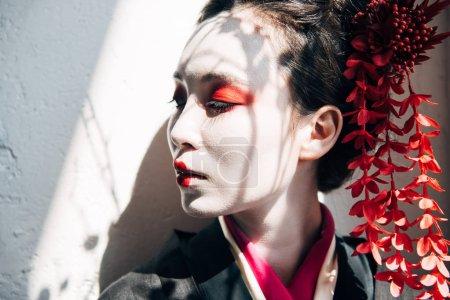 Photo pour Portrait de belle geisha avec le maquillage rouge et blanc dans la lumière du soleil avec des ombres - image libre de droit