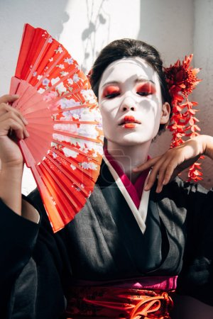 portrait of beautiful geisha with red and white makeup holding hand fan and gesturing in sunlight