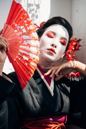 portrait of beautiful geisha with red and white makeup holding hand fan and touching face in sunlight