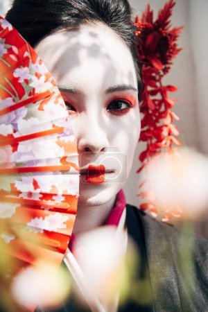 Photo for Selective focus of sakura and beautiful geisha with red and white makeup holding hand fan in sunlight - Royalty Free Image