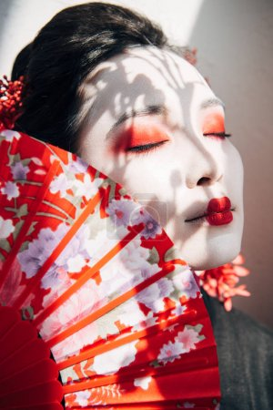 portrait of beautiful geisha with red and white makeup and closed eyes holding hand fan in sunlight