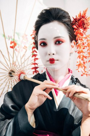 Foto de Hermosa geisha con maquillaje rojo y blanco sosteniendo paraguas en el sol - Imagen libre de derechos