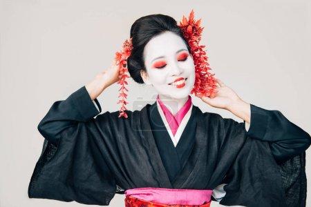 Photo pour Belle geisha en kimono noir souriant isolé sur le blanc - image libre de droit