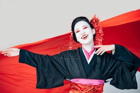 Photo pour Geisha belle heureuse dans le kimono noir avec le tissu rouge sur le fond d'isolement sur le blanc - image libre de droit